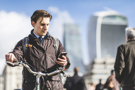UK, London, businessman with bicycle looking at cell phone - WPEF00159