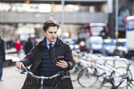 UK, London, businessman pushing  bicycle in the city while looking at cell phone - WPEF00162