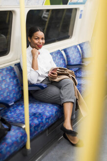 UK, London, portrait of smiling businesswoman with cell phone sitting in underground train - MAUF01367