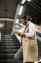 UK, London, smiling businesswoman standing on escalator of underground station looking at cell phone - MAUF01370