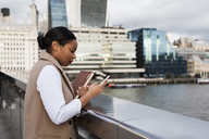 UK, London, businesswoman standing on bridge using cell phone - MAUF01379