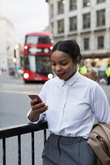 UK, London, smiling businesswoman  looking at cell phone - MAUF01382