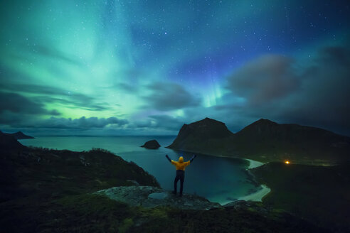 Norway, Lofoten Islands, Haukland Beach, northern lights, man with raised arms - WVF01085