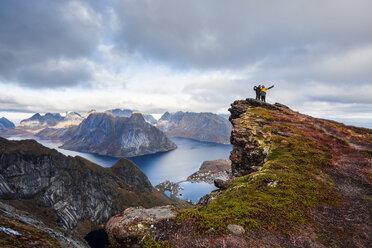 Norway, Lofoten Islands, Reine, men with raised arms standing on Reinebringen - WVF01091