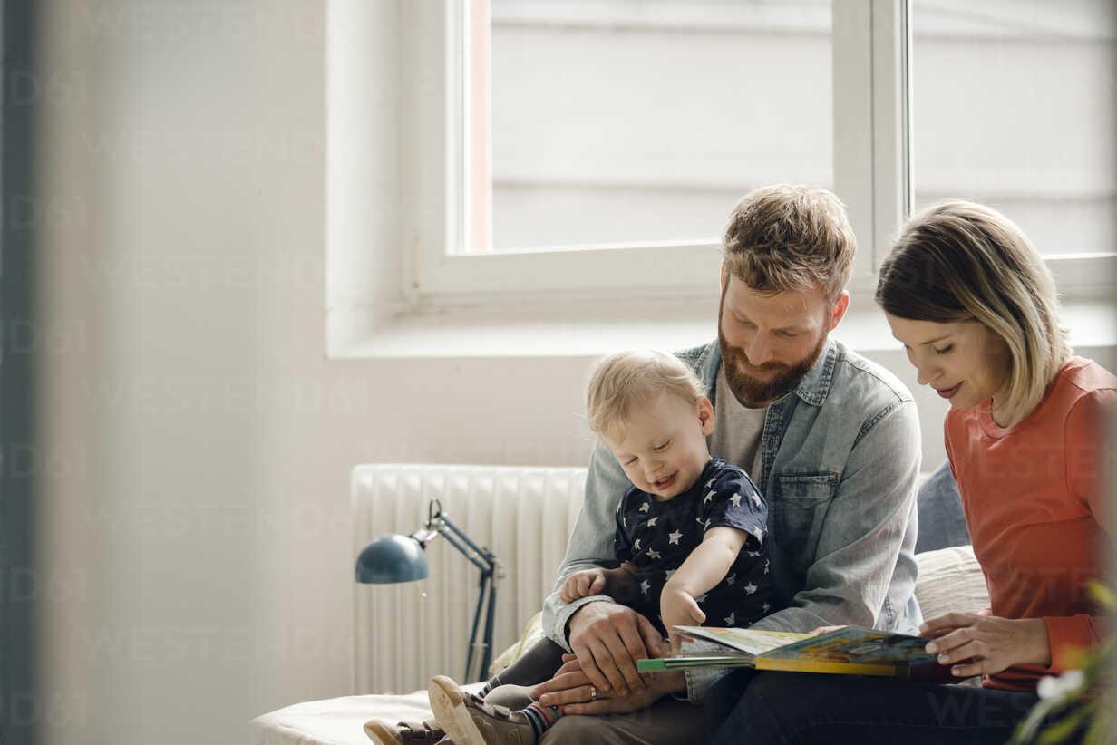 Little boy sittiing on father's lap, mother reading out children's book - KNSF03705 - Kniel Synnatzschke/Westend61