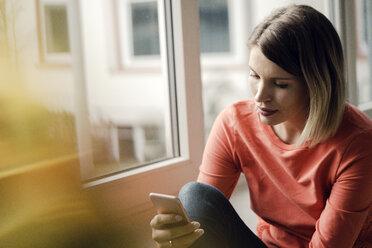 Woman using smartphone at home - KNSF03717