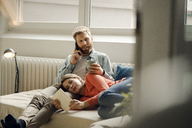 Happy couple reading and cuddling at home - KNSF03729