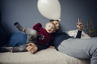 Father reading sms, while son is playing with a balloon - KNSF03759