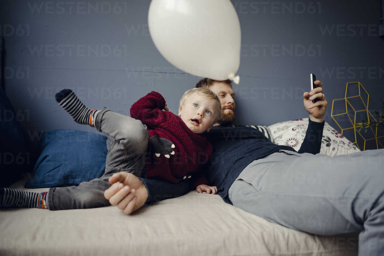 Father reading sms, while son is playing with a balloon - KNSF03759 - Kniel Synnatzschke/Westend61