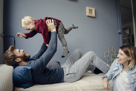 Happy family playing with their son at home - KNSF03762