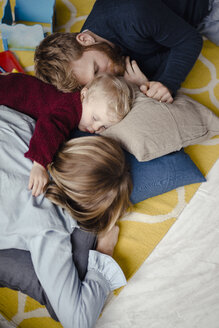 Tiered family resting together on the floor after playing - KNSF03765