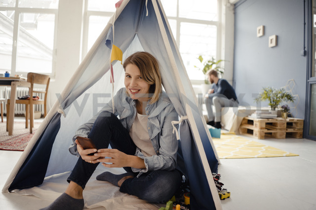 Woman using smartphone in a toy tent, husband sitting in background - KNSF03771 - Kniel Synnatzschke/Westend61
