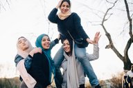 Portrait of cheerful Muslim female friends enjoying against clear sky - MASF00389