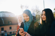 Back lit of smiling young woman using smart phone by female friends in city - MASF00404
