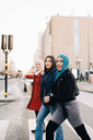 Side view of portrait of smiling female friends crossing street in city - MASF00410