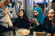 Happy multi-ethnic female friends enjoying at cafe - MASF00413