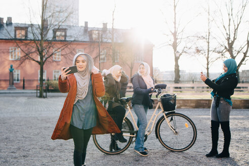 Young woman taking selfie against female friends with bicycle in city - MASF00425