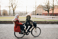 Side view of young woman riding bicycle with female friend on street - MASF00428