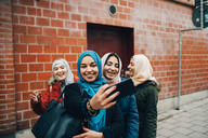 Happy young Muslim woman taking selfie with female friends on sidewalk against building in city - MASF00443