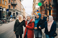 Happy multi-ethnic Muslim female friends standing on street in city - MASF00446