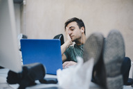 Tired computer programmer using laptop while sitting with feet up at desk in office - MASF00482