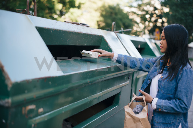 Teenage girl throwing packet in garbage can - MASF00503