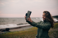Smiling young woman taking selfie on digital tablet at beach - MASF00524