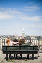 Teenage boy taking selfie with female friends while sitting on bench against sky - MASF00566