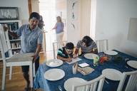 Teenage girl assisting brother in homework while father arranging chairs at dining table - MASF00581