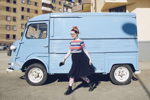 Young woman walking by blue mini van on city street - MASF00602