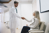 Young male doctor greeting female patient sitting on chair in hospital corridor - MASF00635