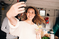 Young woman taking selfie on smart phone with friends in cottage - MASF00662