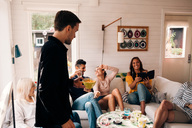 Young man holding bowl of snack while friends enjoying in cottage - MASF00665