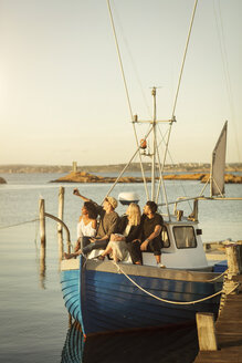 Young man taking selfie with friends while sitting on boat moored at harbor - MASF00674