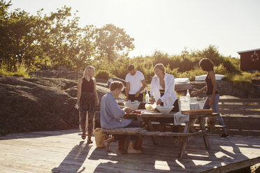 Young multi-ethnic friends at picnic table during summer - MASF00683