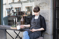 Young female owner using smart phone while sitting with coffee cup by table against store - MASF00686