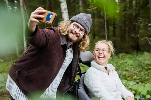 Young male caretaker taking selfie with disabled woman in forest - MASF00698