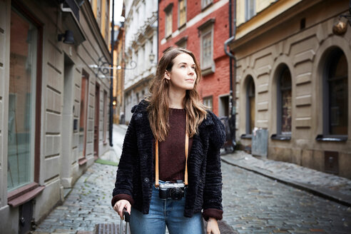 Young woman with camera looking away while standing in alley - MASF00719