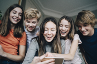 Happy male and female friends taking selfie through smart phone at home - MASF00752
