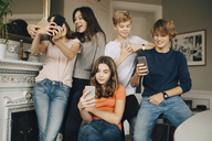 Cheerful friends using smart phones in living room - MASF00758