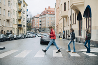 Full length of friends using mobile phone while crossing street in city - MASF00815