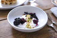 Close-up of yogurt with blackberries and pistachios in bowl at table - MASF00830