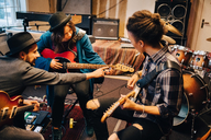Man teaching female friend while playing guitar at recording studio during rehearsals - MASF00851