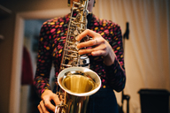 Midsection of woman playing saxophone while practicing at studio - MASF00854