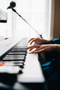 Cropped image of woman playing piano by window at studio - MASF00860