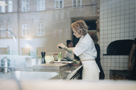 Side view of female chef preparing food at counter with colleagues in kitchen - MASF00869