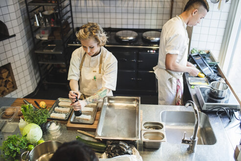 High angle view of female chef preparing food at kitchen counter by male colleague in restaurant - MASF00878