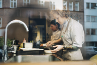 Side view of female chefs preparing food at counter in restaurant kitchen seen from window - MASF00881