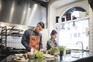 Young male chef preparing food by female colleague at kitchen counter in restaurant - MASF00884