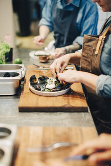 Midsection of chefs preparing food in plate on counter at restaurant kitchen - MASF00890